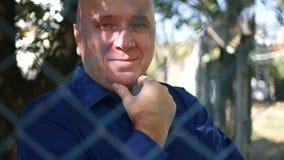 Uomo sulla via indietro di un recinto metallico Looking alla macchina fotografica e del sorriso felice stock footage
