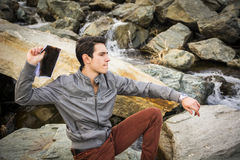 Uomo sulle grandi rocce al fiume che getta qualcosa Immagini Stock Libere da Diritti