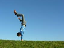 Uomo sulle mani su cielo blu Immagine Stock