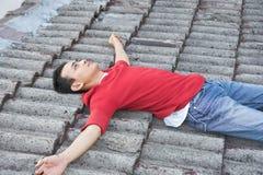 Uomo sulle mattonelle di tetto Immagini Stock