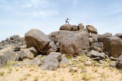 Uomo sulle rocce che indica qualcosa con il suo dito Fotografie Stock Libere da Diritti