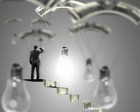 Uomo sulle scale dei soldi che sembrano lampadina con il paracadute dei soldi Immagini Stock Libere da Diritti