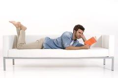 Uomo sullo strato che legge un libro Fotografia Stock