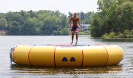Uomo sveglio bello che salta ad un trampolino dell'acqua che galleggia in un lago nel Michigan durante l'estate immagini stock