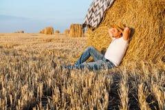 Uomo sveglio che riposa dopo il fieno che raccoglie nei mucchi di fieno Immagini Stock