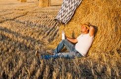 Uomo sveglio che riposa dopo il fieno che raccoglie nei mucchi di fieno Fotografia Stock