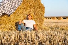 Uomo sveglio che riposa dopo il fieno che raccoglie nei mucchi di fieno Immagini Stock Libere da Diritti