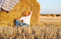Uomo sveglio che riposa dopo il fieno che raccoglie nei mucchi di fieno Fotografia Stock Libera da Diritti