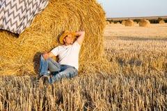 Uomo sveglio che riposa dopo il fieno che raccoglie nei mucchi di fieno Immagine Stock Libera da Diritti