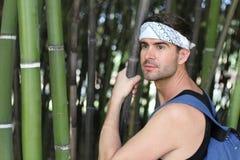 Uomo sveglio in foresta di bambù con distogliere lo sguardo dello spazio della copia Fotografia Stock Libera da Diritti