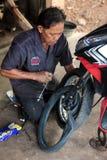 Uomo tailandese che ripara un motociclo Fotografia Stock