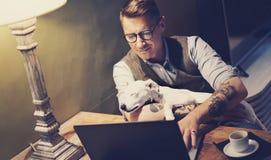 Uomo tatuato bello in occhiali che funzionano a casa sul computer portatile mentre sedendosi alla tavola di legno con il sonno sv Fotografia Stock Libera da Diritti