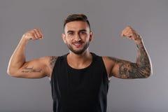 Uomo tatuato sorridente che mostra il bicipite fotografia stock libera da diritti
