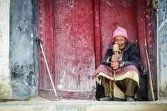 Uomo tibetano che si siede e che prega alla casa fotografie stock libere da diritti