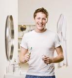 Uomo in toothbrush e dentifricio in pasta della holding della stanza da bagno Immagini Stock
