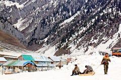 Uomo tre con il waitng della slitta l'un uomo turistico che sledding nella neve, il Jammu e Kashmir, India - 4 aprile 2012 Immagine Stock