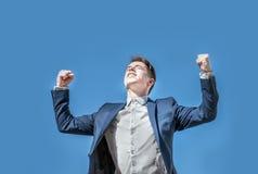 Uomo trionfante di affari che aumenta le sue armi sopra il fondo del cielo blu Immagine Stock Libera da Diritti