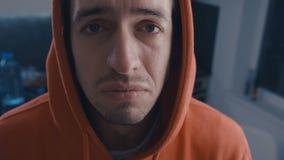 Uomo triste in cappuccio che grida con gli strappi a casa Concetto di dramma stock footage