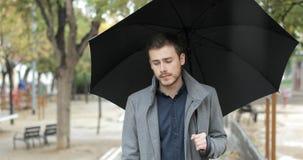 Uomo triste che cammina da solo in un giorno piovoso dell'inverno stock footage