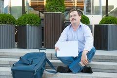 Uomo triste che si siede sui punti con un segno vuoto della valigia Fotografie Stock