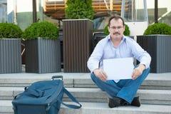 Uomo triste che si siede sui punti con un segno vuoto della valigia Fotografia Stock
