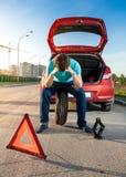 Uomo triste che si siede sulla ruota di riserva vicino all'automobile rotta Immagini Stock