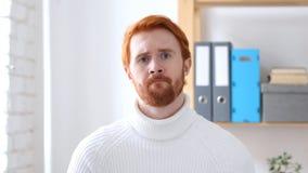 Uomo triste con i capelli rossi che ritengono ribaltamento, preoccupato Immagine Stock