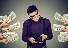 Uomo triste con il portafoglio vuoto che è offerto le banconote del dollaro dei soldi Fotografie Stock Libere da Diritti