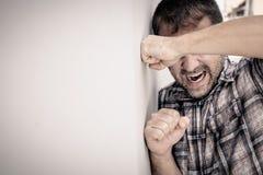 Uomo triste del ritratto uno che sta vicino ad una parete ed alle coperture il suo fronte Immagini Stock Libere da Diritti