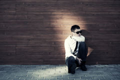 Uomo triste di affari nella depressione che si siede alla parete Fotografia Stock