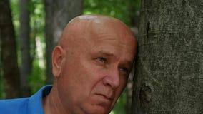 Uomo triste e deludente che si siede vicino ad un albero nella foresta stock footage