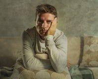Uomo triste e disperato giovane a casa che si siede alla depressione ed allo sforzo di sofferenza dello strato del sofà che riten Immagine Stock