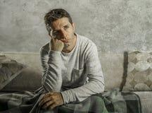 Uomo triste e disperato giovane a casa che si siede alla depressione ed allo sforzo di sofferenza dello strato del sofà che riten Fotografia Stock