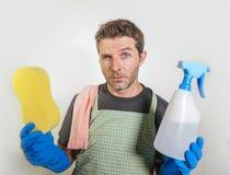 Uomo triste e stanco isolato nella spugna domestica della tenuta di sforzo di pulizia e spruzzo del sapone del detersivo che semb fotografia stock