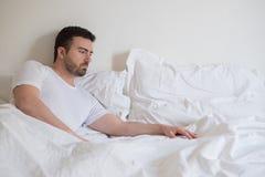 Uomo triste e turbato che sveglia da solo di mattina Immagine Stock