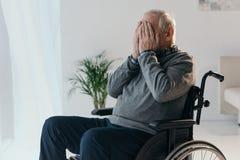 Uomo triste senior in sedia a rotelle che copre il suo fronte immagine stock libera da diritti