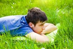 Uomo triste sull'erba fotografie stock