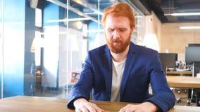 Uomo triste turbato in ufficio che ritiene capelli imbarazzati e rossi Immagini Stock