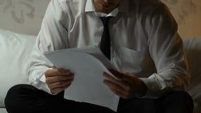 Uomo turbato che guarda attraverso i documenti di divorzio, sedentesi nella camera di albergo, disfacimento video d archivio