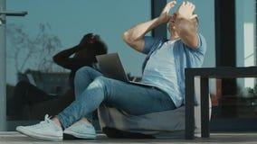 Uomo turbato che lavora al computer portatile Specialista preoccupato che si siede con il taccuino all'aperto video d archivio