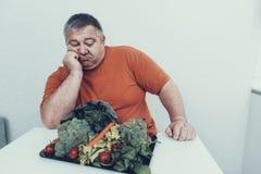 Uomo turbato del grasso con Tray With Vegetarian Food fotografia stock libera da diritti