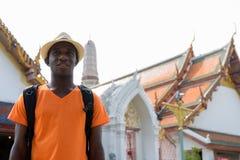 Uomo turistico africano felice che sorride e che pensa al tempio buddista fotografia stock libera da diritti