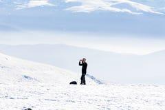 Uomo turistico che fa le foto in un'alta montagna di inverno Immagini Stock Libere da Diritti