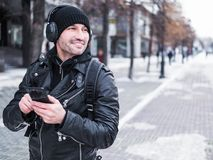 Uomo turistico che per mezzo dello smartphone per ascoltare la musica tramite cuffie mentre camminando dalla città di inverno fotografia stock libera da diritti