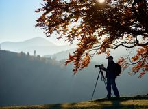 Uomo turistico della viandante con la macchina fotografica sulla valle erbosa su fondo del paesaggio della montagna sotto il gran fotografia stock libera da diritti
