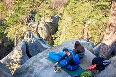 Uomo turistico e ragazza che si siedono in sacchi a pelo sulla grande roccia della montagna Immagine Stock
