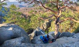 Uomo turistico e ragazza che si siedono in sacchi a pelo sulla grande roccia della montagna Fotografia Stock Libera da Diritti