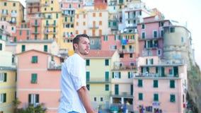 Uomo turistico giovane con la grande vista del villaggio sbalorditivo di Manarola, Cinque Terre, Liguria, Italia archivi video