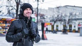 Uomo turistico sorridente, camminando dalla città di inverno ed ascoltando la musica tramite cuffie immagine stock libera da diritti