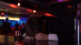Uomo ubriaco che dorme sul contatore della barra, depressione di sofferenza, concetto di abuso di alcool video d archivio